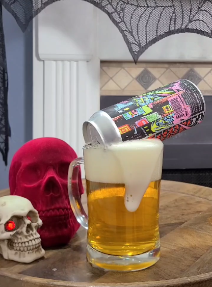 Prankensteiner Beer by Solemn Oath Brewery being poured into large beer glass next to large Red skull and small skull with red eyes.
