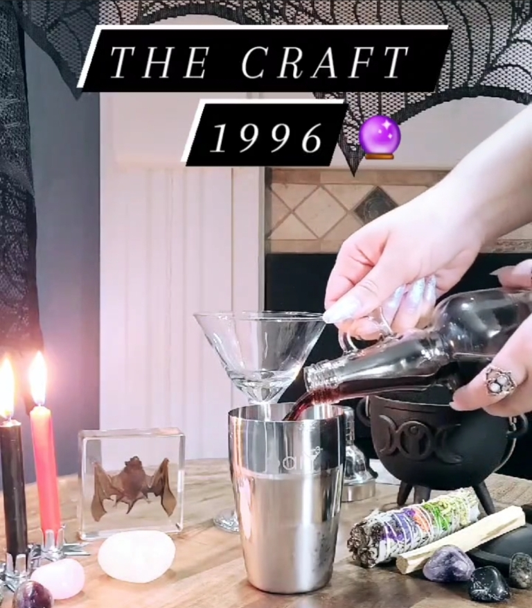 B****craft drink made for the episode covering The Craft. Black and red lit candle. Bat in glass cube. Stones, sage, couldron in background. Drink is poured into shaker.