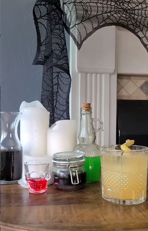 The cure drink garnished with ginger on a table alongside a red skull shot glass, black liquid in a jar, green liquid in a jar, and white candles.