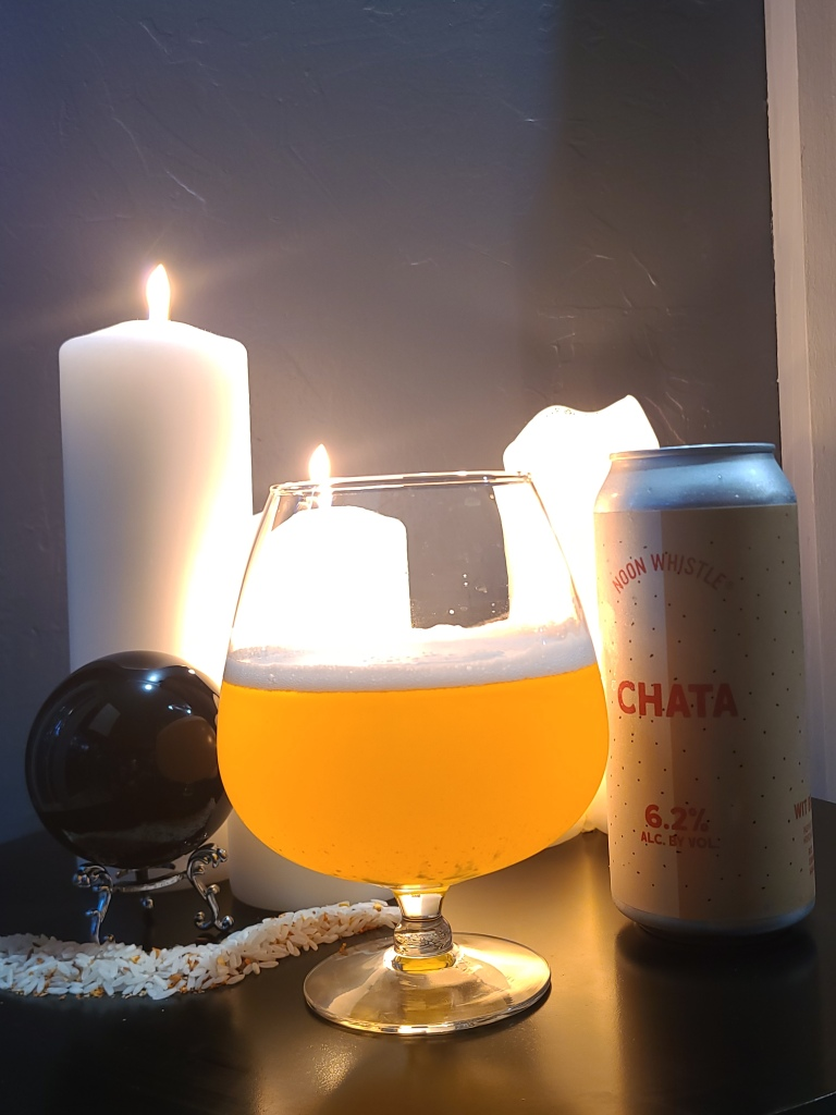 The Chata beer was poured into a round glass and sits on the table with the can of Chata from Noon Whistle Brewing. There is also a black crystal ball, rice and spices, and lit white candles in the background.