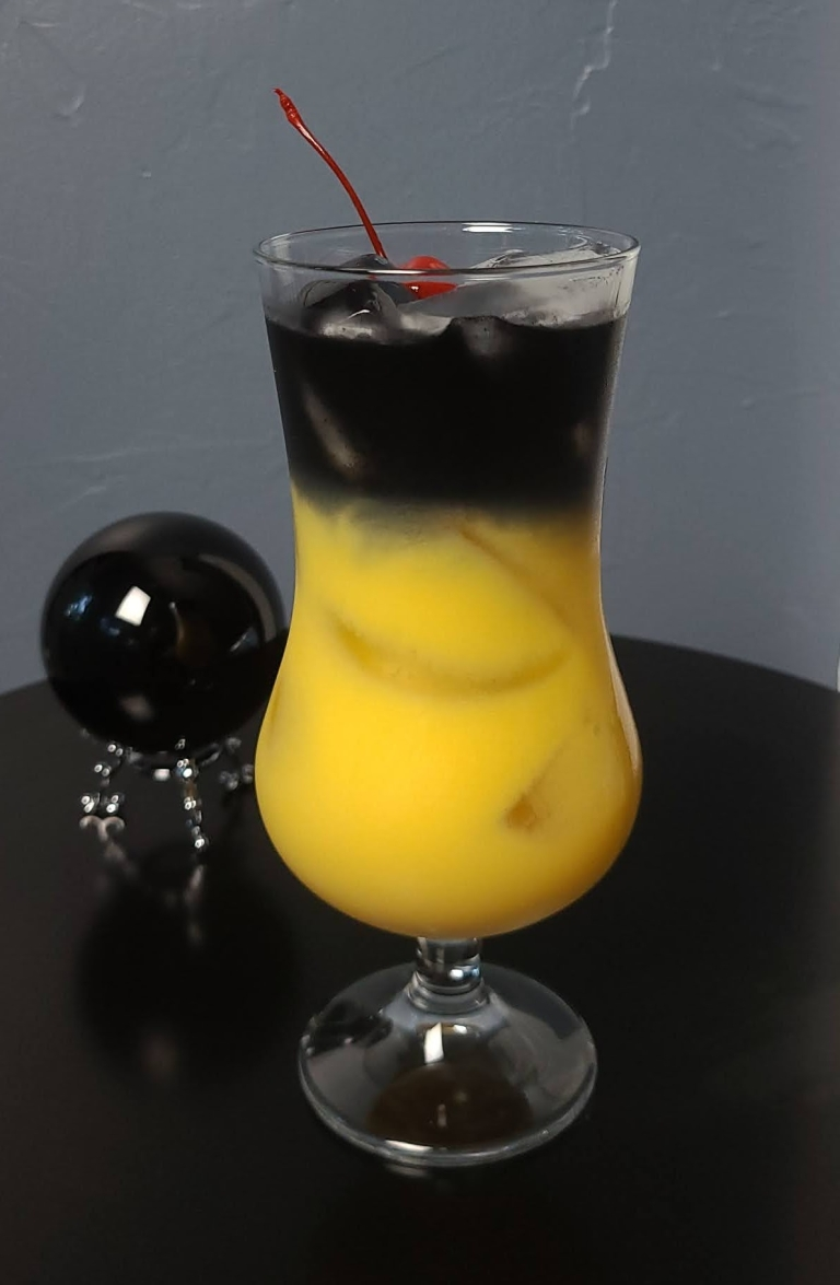 Black magic cocktail sits on black table with black crystal ball in background. Drink consists of orange juice with black vodka layered at the top. Maraschino cherry used for garnish.