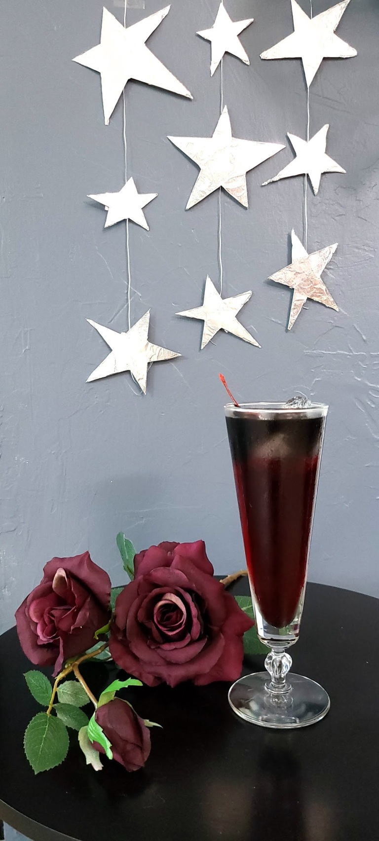 Shiny stars hang in the background. Red roses lay on black table next to glass. Glass has the Pig's Blood drink garnished with Cherry. The drink is red with black layered on top.