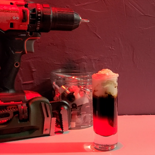 Jig shot sits in front of power drill, wrench, and jar of screws, bolts, etc. Shot has grenadine for red, coffee liqueur for black, and heavy whipping cream with vodka for white.