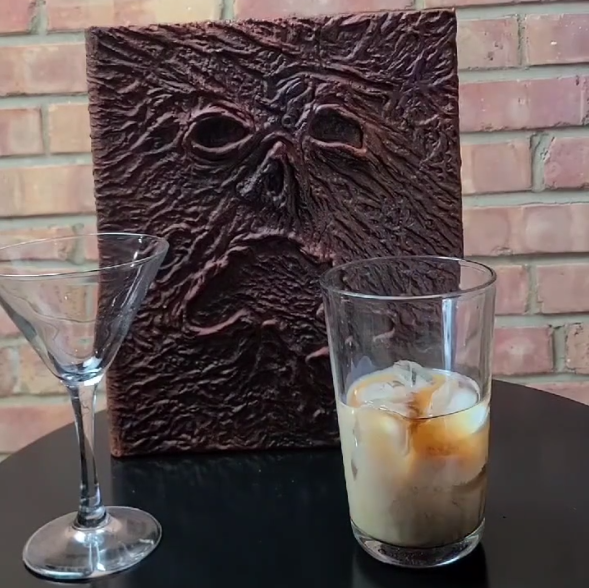 A martini glass and a mixing glass sit on a black table. The mixing glass has ice and a few of the ingredients needed to make the Coffeenomicon. The Necronomicon book sits and watches.