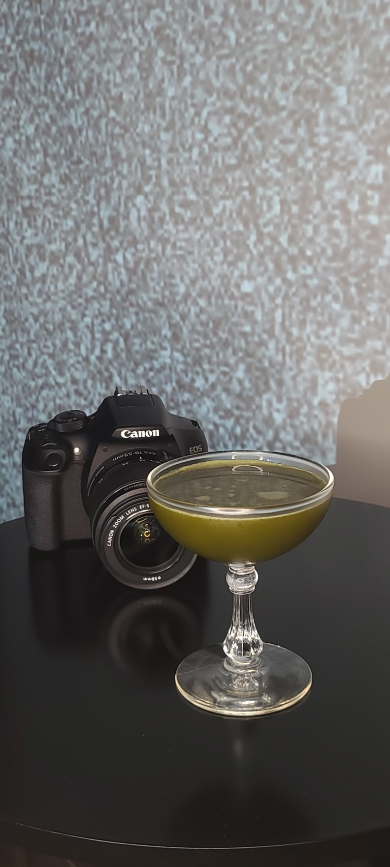 A screen with white noise in the background. A camera sits on a black table. The drink called Well Water sits in a glass. The drink is a nasty tint of green like the well water from the movie The Ring.