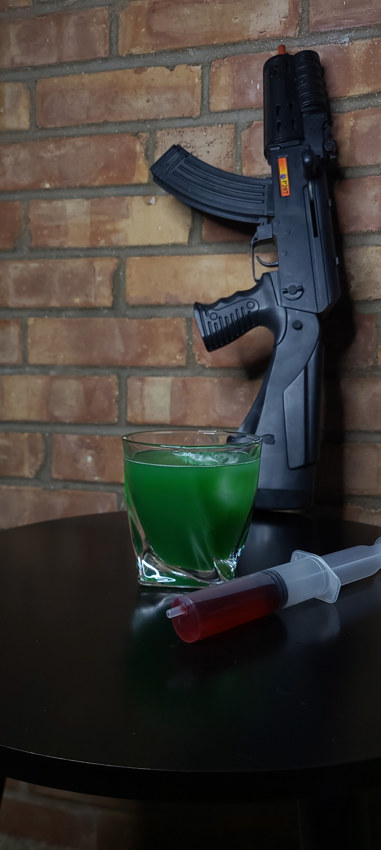 Green drink named 28 Days of Menthe sits in twisted glass with ice. Red syringe sits on black table with gun in the background on brick wall.