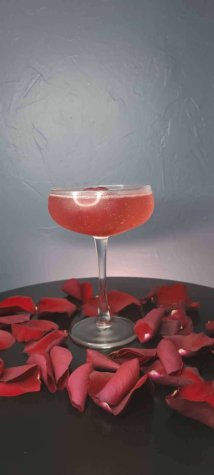 The Rejected Proposal drink sits on black table in front of dark blue wall. Rose pedals surround the base of the drink. The drink is red and in a coupe glass.