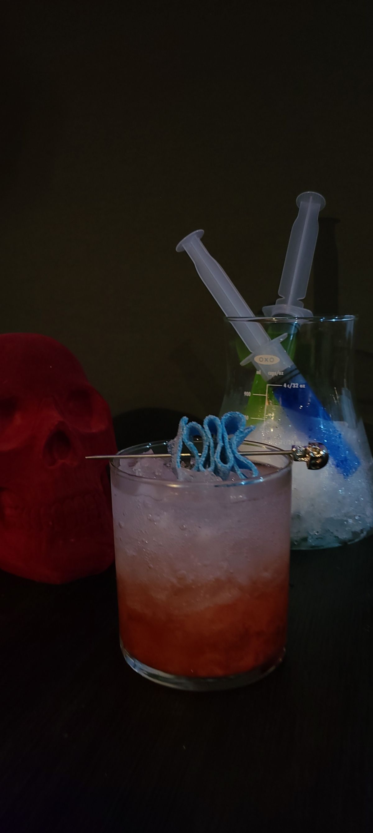 Red Queen Bramble drinks sits on black table. The drink is red and has a skewered blue candy on top to act as the T-Virus. In the background a red skull sits with a beaker. The beaker has ice with two syringes containing a blue liquid (T-Virus) and a green liquid (Antivirus).