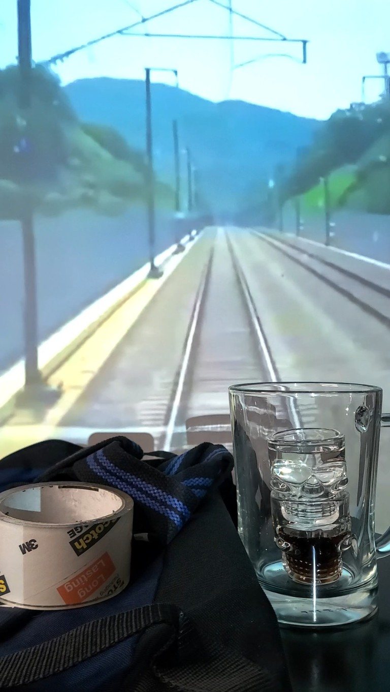 Background is the pov of a train on train tracks. A duffle bag on the table with wrist wraps and tape. A mug sits on the table with a shot glass half full of Dr. Pepper Zero and a shot glass full of Soju in the center.