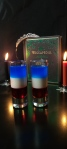 9/11 Tribute Shots sit in center of black table. The shot is layered red, white, and blue. In the background there is a lit black candle and a lit red candle. In between is a green Wiccapedia book with a tiara on top.