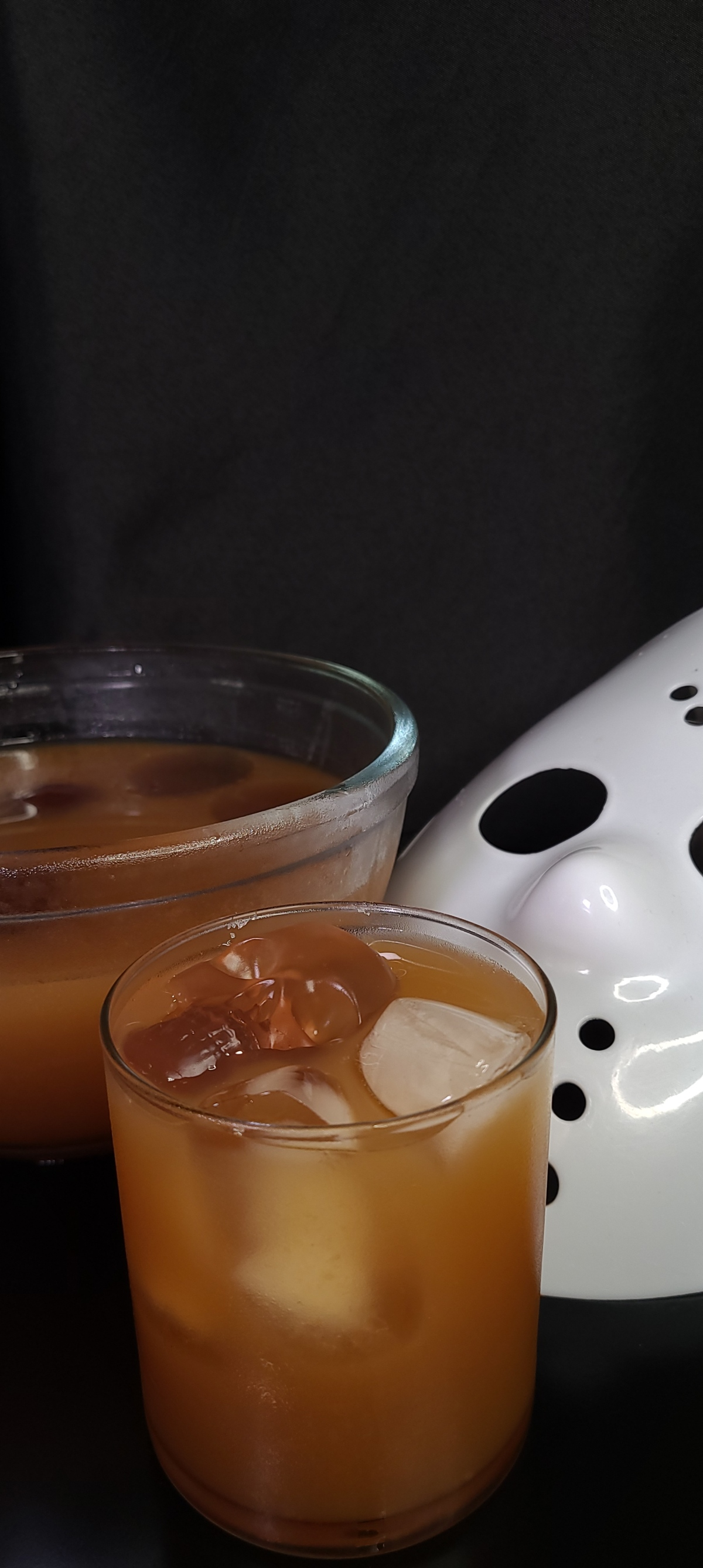 The Jason, Listen to Mother's Shrunken Head sits on a black table with a black background and a hockey mask. A punch bowl also sits in the background with jello skulls floating on top. The drink has one skull with ice.
